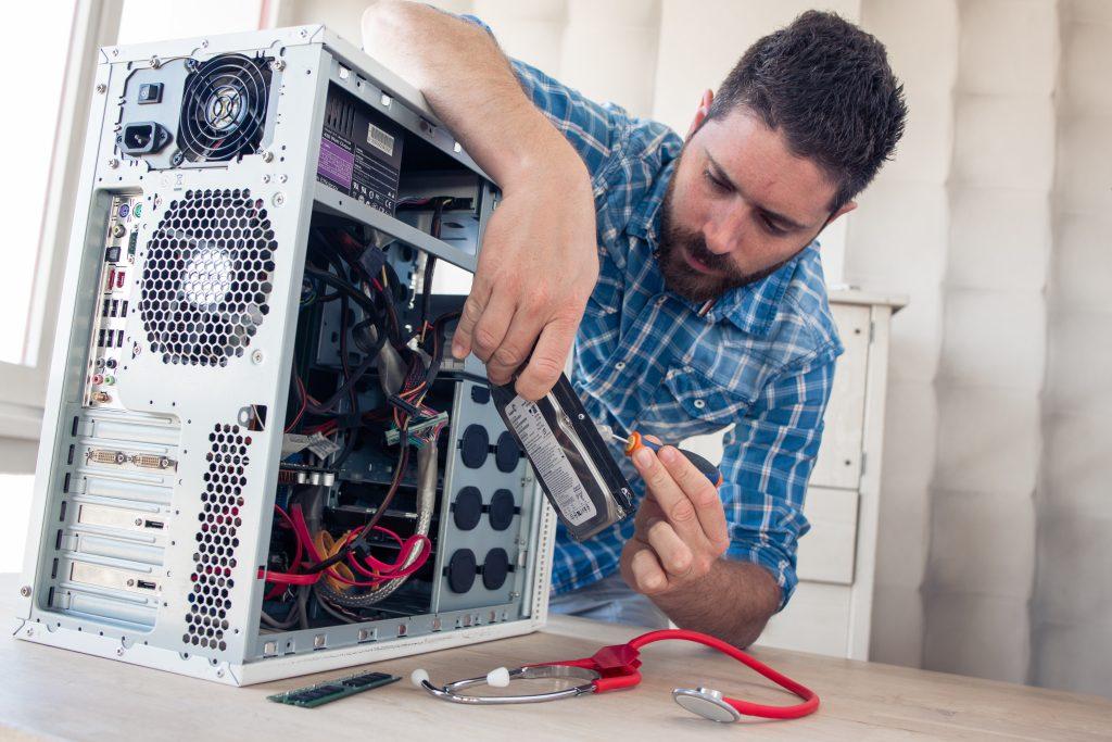 Das Bild zeigt einen Mann bei der Reparatur einer Festplatte.