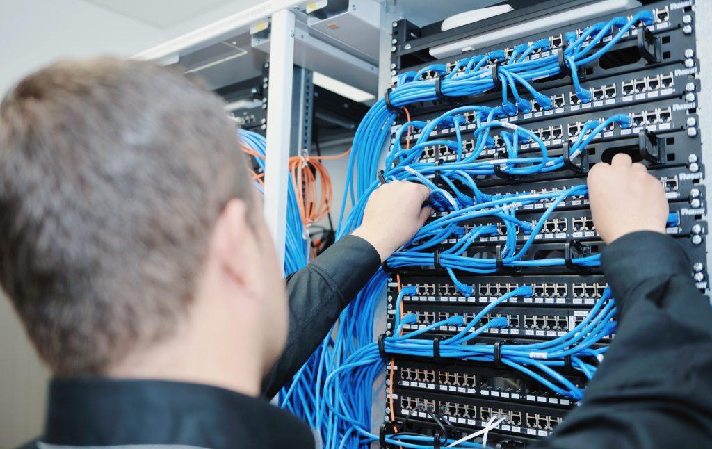 Das Bild zeigt einen Mann, bei der Arbeit an einem Server.