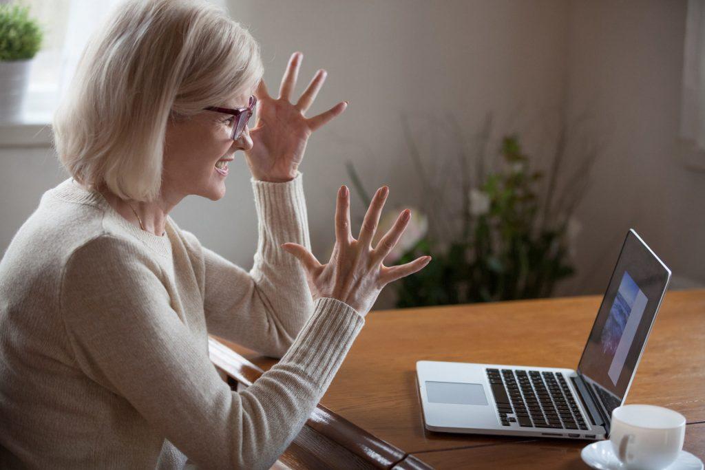 Das Bild zeigt eine genervte Frau vor Ihrem Laptop.