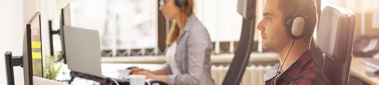Das Bild zeigt ein Mann und eine Frau an ihrem Arbeitsplatz vor dem Computer.